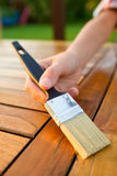 Hand holding a brush applying varnish paint on a wooden garden table Stock Photo
