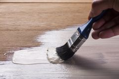 Hand holding a brush applying  varnish paint. On a wooden surface Royalty Free Stock Photography