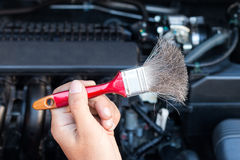 Hand holding brush for cleaning car engine. Transport concept Royalty Free Stock Image