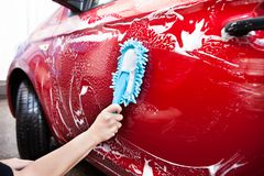 Hand holding brush over car Stock Image