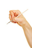 Hand holding brush while painting. Side view of hand holding a brush while painting Stock Image