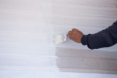 Hand holding brush painting timber wall Stock Image