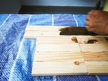 Hand holding brush shows how to apply stain to wood planks. stock photos
