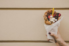 Hand holding bubble waffle with fruits, chocolate and marshmallow, with copy space.  Royalty Free Stock Image