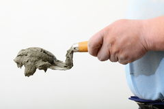 Hand holding a bucket trowel with cement mortar Stock Photo