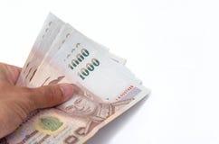 Hand holding a bulk of 1000 baht Stock Photography