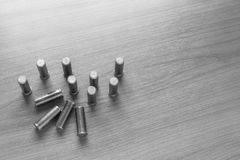 Hand holding .38 bullet. 38 flat head bullet on wooden table with light above, black and white tone, selective focus Royalty Free Stock Photos