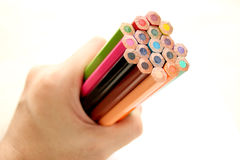 Hand holding bunch of color pencils. A Hand holding set of color pencils on white background stock photos