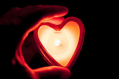 Hand holding burning candle heart Stock Photos