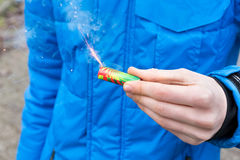 Hand holding burning firework in front of blue jacket Stock Images