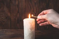 Hand holding a burning match and lights a candle royalty free stock photos