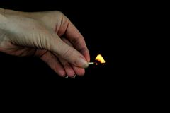 Hand holding burning match stick Stock Photography