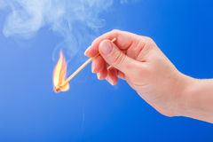 Hand holding a burning matchstick Stock Image
