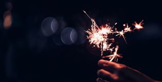 Hand holding burning Sparkler blast on a black bokeh background royalty free stock image