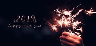 Hand holding burning Sparkler blast with happy new year 2019 on. A black bokeh background at night,holiday celebration event party,dark vintage tone royalty free stock photography