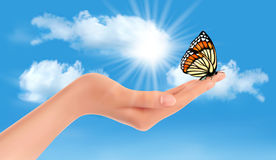 Hand holding a butterfly against a blue sky and su