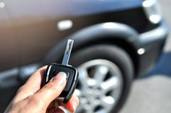 Hand holding button on the remote car. In selective focus of woman hand presses on the remote control car alarm systems. Auto insurance business.Car security royalty free stock photography