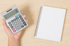 Hand holding calculator and put notebook on wood Royalty Free Stock Images