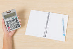 Hand holding calculator and put pen and notebook on wood Royalty Free Stock Photos