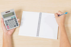 Hand holding calculator and writting on notebook Royalty Free Stock Images