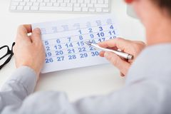 Hand holding calendar and pen Stock Photo
