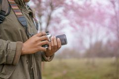 Hand holding camera with beautiful natural. Background Royalty Free Stock Photo