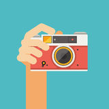Hand holding camera on blue background Stock Photos
