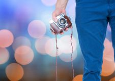 Hand holding camera with sparkling light bokeh background Royalty Free Stock Photography
