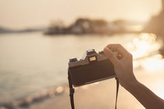 Hand holding camera to take photo of the beautiful sunset Royalty Free Stock Photos