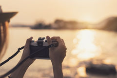 Hand holding camera to take photo of the beautiful sunset. On the beach, Travel concept Royalty Free Stock Photo