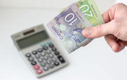 Hand holding canadian money with calculator blurred in background. Horizontal image of a hand holding a 20 and 10 dollar canadian dollar bill with calculator Royalty Free Stock Photo