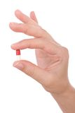 Hand holding a capsule or pill Stock Images