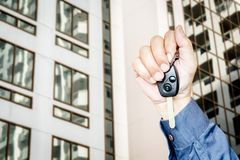 Hand holding car key. On building background Stock Photography