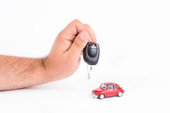 Hand holding car key and a car. Isolated on white background royalty free stock photography