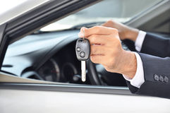 Hand holding a car key - car sale & rental business concept