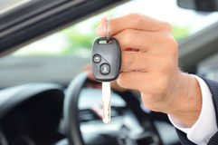 Hand holding a car key - car sale & rental business concept Stock Photos