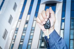Hand holding car key. On building background Royalty Free Stock Image