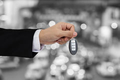 Hand holding car key remote with Bokeh of car traffic background Royalty Free Stock Photo