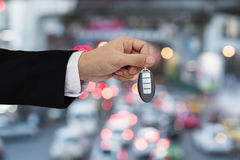 Hand holding car key remote with Bokeh of car traffic background Stock Photos