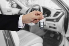 Hand holding car key remote, with modern car background Stock Image