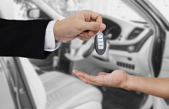 Hand holding car key remote, with modern car background Royalty Free Stock Photography