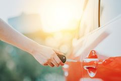Hand holding car key unlocking a car door Royalty Free Stock Photography