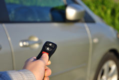 A hand holding car keys. And a remote control for keyless entry Stock Image