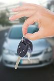 Hand holding a car keys. With a car on background Royalty Free Stock Photography