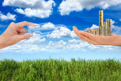 Hand holding car and money. In green grass blue sky Stock Photos