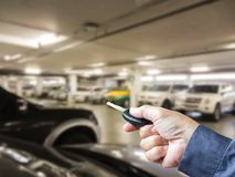 Hand holding car remote on Blurred image parking in the mall. Hand holding car remote on a Blurred image parking in the mall Royalty Free Stock Images