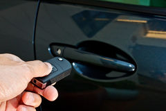 A hand holding car's remote control Royalty Free Stock Photo