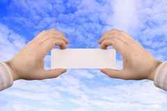 Hand holding card. Holding businesscard with the sky as background Stock Image