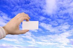 Hand holding card. Holding businesscard with the sky as background Royalty Free Stock Photo