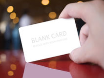 Hand holding card. Hand holding white dummy card (to be replaced with your own) in the elegance atmosphere Stock Images